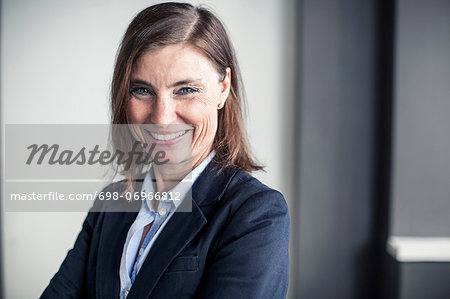 Portrait of happy mature businesswoman standing in office Stock Photo - Premium Royalty-Free, Image code: 698-06966812