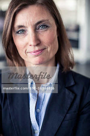 Portrait of businesswoman smiling in office Stock Photo - Premium Royalty-Free, Image code: 698-06966816