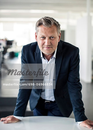 Portrait of mature businessman leaning on desk in office Stock Photo - Premium Royalty-Free, Image code: 698-06966834
