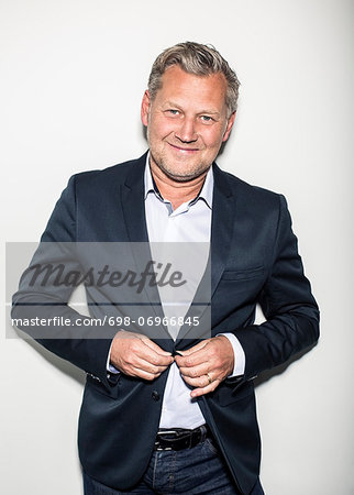 Portrait of mature businessman wearing suit while standing against wall Stock Photo - Premium Royalty-Free, Image code: 698-06966845