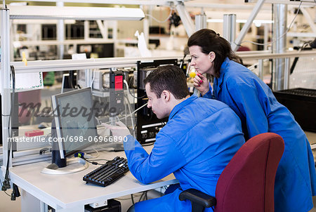 Male electrician pointing at computer monitor while discussing with colleague in industry Stock Photo - Premium Royalty-Free, Image code: 698-06966890