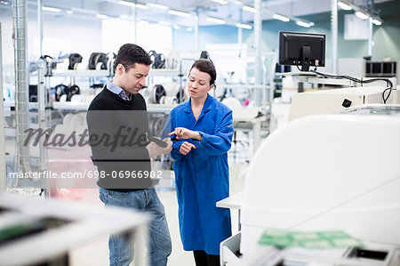 Mid adult female technician explaining machine part to client in factory Stock Photo - Premium Royalty-Free, Image code: 698-06966902