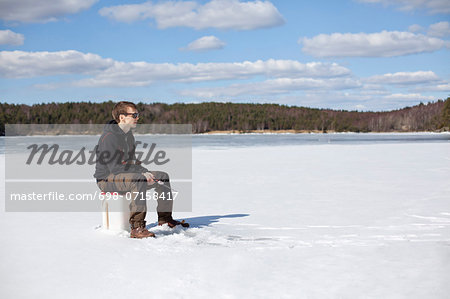 Young man ice fishing on frozen lake Stock Photo - Premium Royalty-Free, Image code: 698-07158417