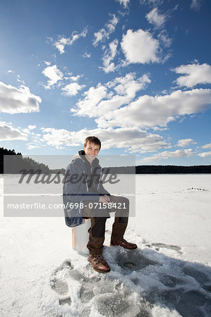 Portrait of happy young man ice fishing on frozen lake Stock Photo - Premium Royalty-Free, Image code: 698-07158421
