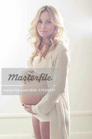Portrait of pregnant woman holding abdomen at home Stock Photo - Premium Royalty-Free, Image code: 698-07158437