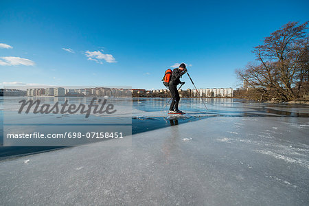 Full length of man skating on frozen lake Stock Photo - Premium Royalty-Free, Image code: 698-07158451