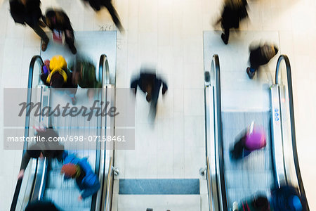 Blurred motion of people using escalator in mall Stock Photo - Premium Royalty-Free, Image code: 698-07158461
