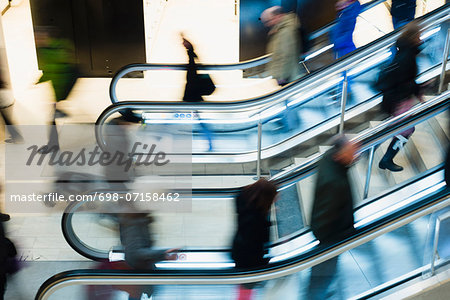 High angle view of people using escalator in shopping mall Stock Photo - Premium Royalty-Free, Image code: 698-07158462