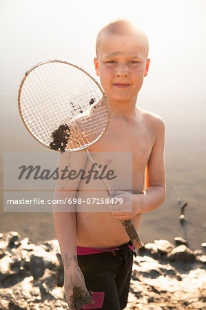 Shirtless boy holding badminton racket on beach Stock Photo - Premium Royalty-Free, Image code: 698-07158479