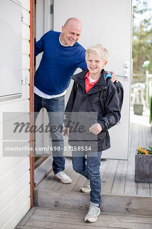 Portrait of happy boy leaving for school while father looking at him Stock Photo - Premium Royalty-Free, Image code: 698-07158534