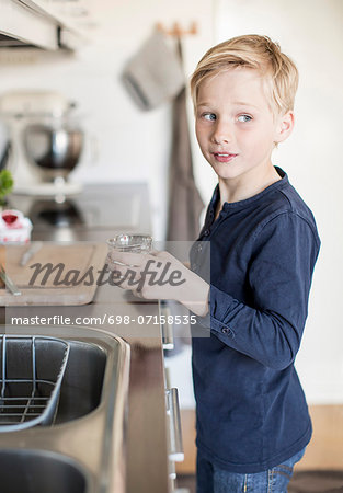 Side view of boy holding glass while looking away in kitchen Stock Photo - Premium Royalty-Free, Image code: 698-07158535
