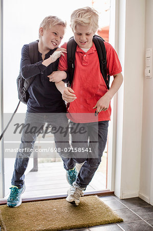 Boys pushing each other while entering home from school Stock Photo - Premium Royalty-Free, Image code: 698-07158541