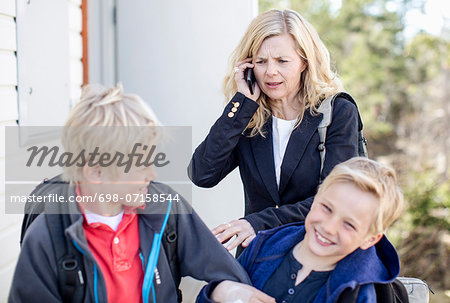 Irritated mother using mobile phone while stopping mischievous sons Stock Photo - Premium Royalty-Free, Image code: 698-07158544