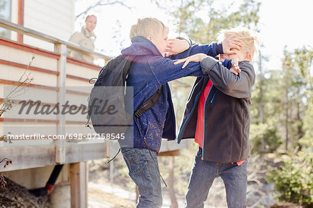 Brothers fighting while mother looking at them from balcony Stock Photo - Premium Royalty-Free, Image code: 698-07158545