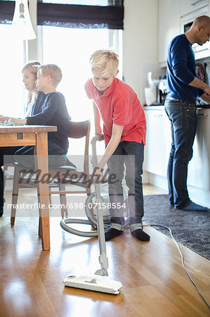 Boy vacuuming hardwood floor with family in background Stock Photo - Premium Royalty-Free, Image code: 698-07158554