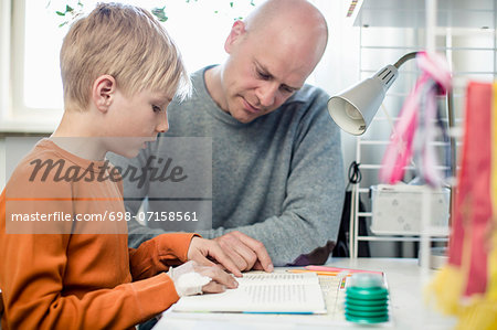 Father helping son with homework at table Stock Photo - Premium Royalty-Free, Image code: 698-07158561