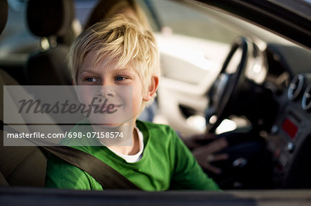 Smiling little boy looking through car window Stock Photo - Premium Royalty-Free, Image code: 698-07158574