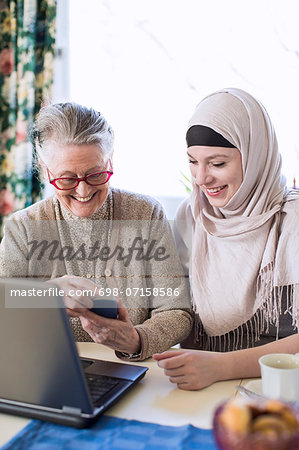 Senior woman with female home caregiver visiting bank through laptop at home Stock Photo - Premium Royalty-Free, Image code: 698-07158586