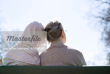Rear view of senior woman and female home caregiver sitting together on park bench Stock Photo - Premium Royalty-Free, Image code: 698-07158599