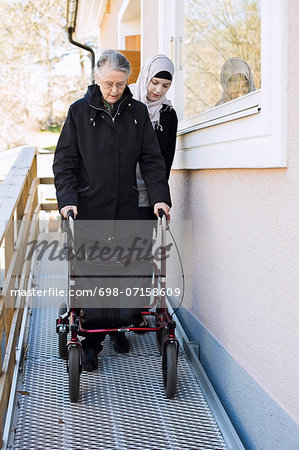 Female home caregiver helping senior woman with walking frame through passage Stock Photo - Premium Royalty-Free, Image code: 698-07158609
