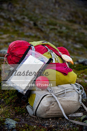 Hiking backpack with sleeping bag and map in forest Stock Photo - Premium Royalty-Free, Image code: 698-07158623