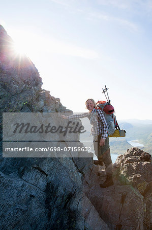 Portrait of happy female climber standing on rocks against sky Stock Photo - Premium Royalty-Free, Image code: 698-07158632