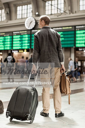 Businessman with luggage standing on railway station Stock Photo - Premium Royalty-Free, Image code: 698-07158653