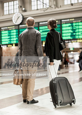 Business people with luggage standing on railway station Stock Photo - Premium Royalty-Free, Image code: 698-07158654
