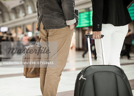 Midsection of business people with luggage standing on railway station Stock Photo - Premium Royalty-Free, Image code: 698-07158655