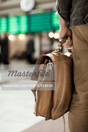 Midsection of businessman carrying bag while standing on railway station Stock Photo - Premium Royalty-Free, Image code: 698-07158656