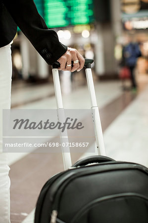 Midsection of businessman carrying bag while standing on railway station Stock Photo - Premium Royalty-Free, Image code: 698-07158657