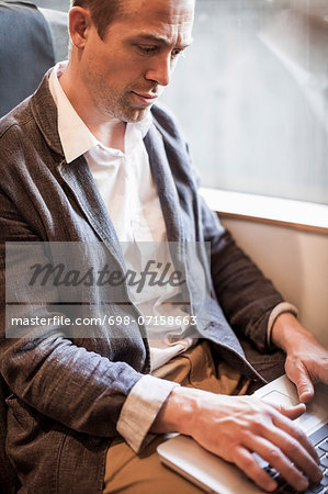 Mature businessman using laptop in train Stock Photo - Premium Royalty-Free, Image code: 698-07158663