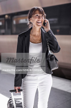Happy businesswoman using mobile phone on railroad station platform Stock Photo - Premium Royalty-Free, Image code: 698-07158665