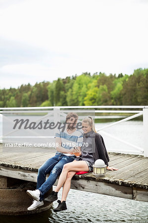 Couple using mobile phone together on pier Stock Photo - Premium Royalty-Free, Image code: 698-07158670