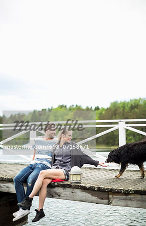 Couple with dog on pier Stock Photo - Premium Royalty-Free, Image code: 698-07158671