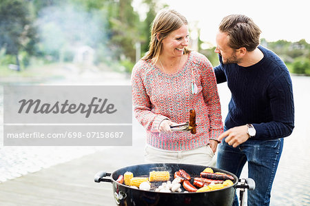 Happy couple looking at each other while barbecuing on pier Stock Photo - Premium Royalty-Free, Image code: 698-07158687
