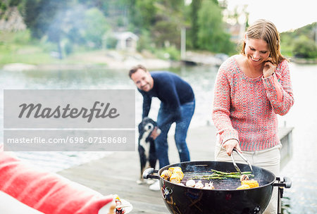 Happy woman using mobile phone while barbecuing with man and dog in background on pier Stock Photo - Premium Royalty-Free, Image code: 698-07158688