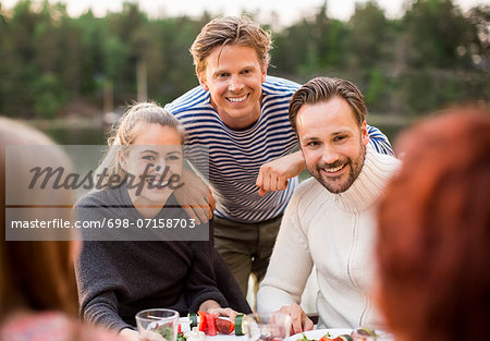 Happy friends enjoying meal outdoors Stock Photo - Premium Royalty-Free, Image code: 698-07158703