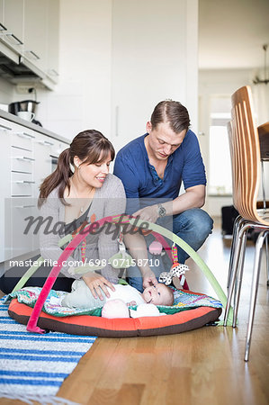 Parents caressing baby girl lying in play mat at kitchen Stock Photo - Premium Royalty-Free, Image code: 698-07158710