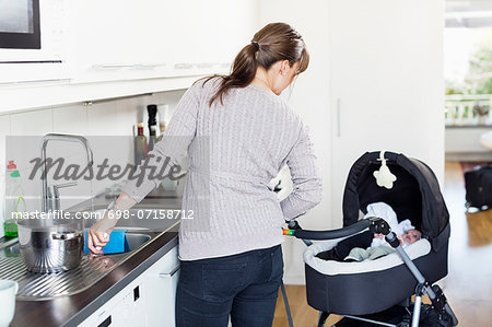Rear view of woman looking at baby girl in carriage while washing utensils in kitchen Stock Photo - Premium Royalty-Free, Image code: 698-07158712
