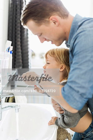 Father and daughter at bathroom sink Stock Photo - Premium Royalty-Free, Image code: 698-07158720