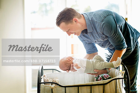 Father putting baby girl in cradle at home Stock Photo - Premium Royalty-Free, Image code: 698-07158723