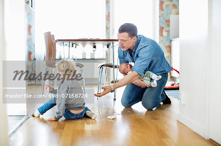 Father holding baby girl while cleaning floor with daughter at home Stock Photo - Premium Royalty-Free, Image code: 698-07158728