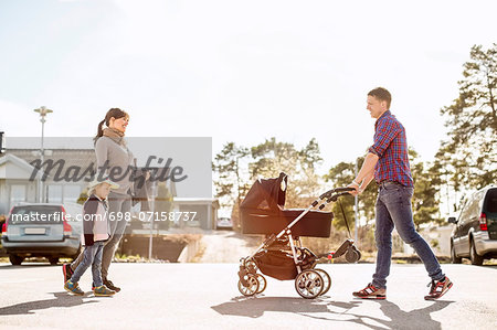 Side view of parents with baby carriage and daughter walking on street Stock Photo - Premium Royalty-Free, Image code: 698-07158737