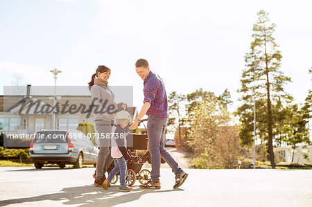 Parents with baby carriage and daughter on street Stock Photo - Premium Royalty-Free, Image code: 698-07158738
