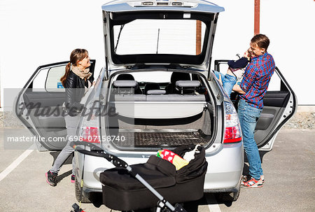 Family entering into car on street Stock Photo - Premium Royalty-Free, Image code: 698-07158740