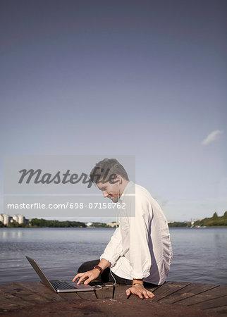Businessman listening to music while using laptop on boardwalk at seaside Stock Photo - Premium Royalty-Free, Image code: 698-07158762
