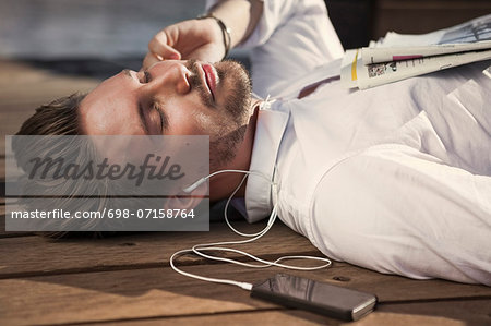Businessman listening music while lying on boardwalk Stock Photo - Premium Royalty-Free, Image code: 698-07158764
