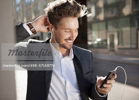 Young businessman smiling while listening music through mobile phone on street Stock Photo - Premium Royalty-Free, Image code: 698-07158774