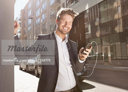 Happy young businessman listening music through mobile phone on street Stock Photo - Premium Royalty-Free, Image code: 698-07158775